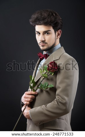 Handsome man with a single red rose - stock photo