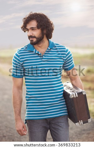 handsome man with afro hair posing for the camera - stock photo