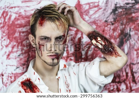 Handsome man with an open fracture of the hand, white bones of the forearm dropped out, a painful injury, scars on face. Standing near bloody wall background, scene from horror film or Halloween party - stock photo