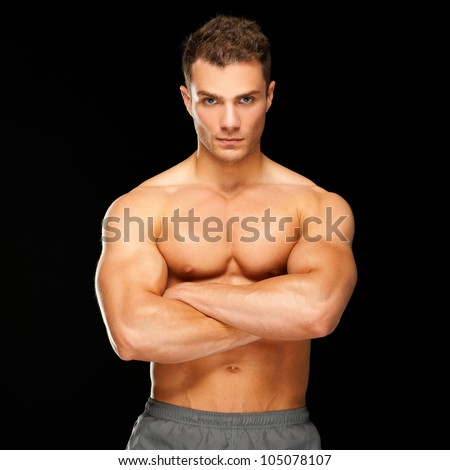 Handsome man with arms crossed looking his left on black background - stock photo