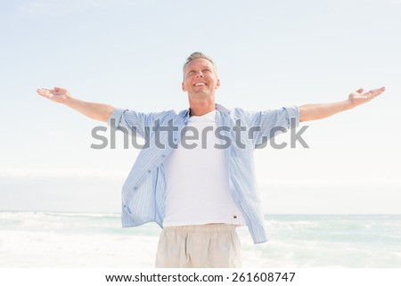 Handsome man with arms outstretched at the beach - stock photo
