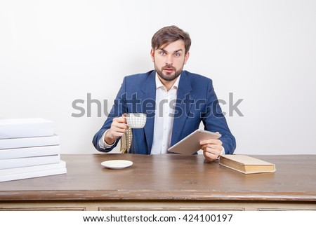 Handsome man with beard and brown hair and blue suit and tablet pc computer and some books and cup drinking coffee or tea sitting, looking at camera and surprised.  Isolated on white background.   - stock photo