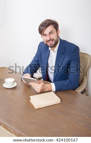 Handsome man with beard and brown hair and blue suit and tablet pc computer and some books holding tablet sitting in the office and looking at camera with smile.  Isolated on white background.   - stock photo