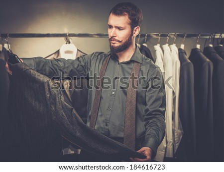 Handsome man with beard choosing jacket in a shop - stock photo