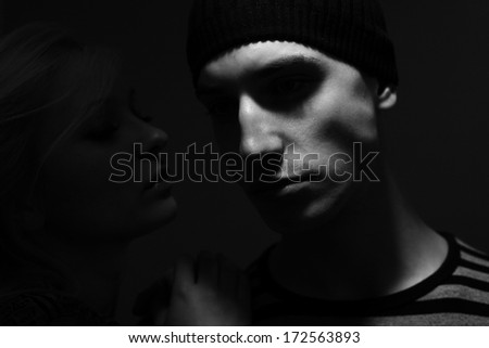 handsome man with cap handsome man with hat whispers to him and young woman whispers to him  - stock photo
