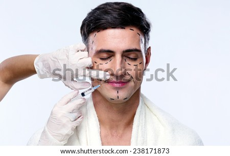 Handsome man with closed at plastic surgery with syringe in his face - stock photo