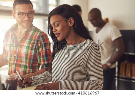 Handsome man with eyeglasses and beautiful woman in striped long sleeve shirt working at desk with co-workers in background - stock photo