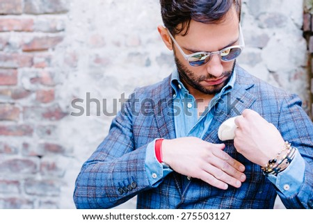 Handsome man with glasses in a suit, against old vintage wall, fixing his pocket square - stock photo