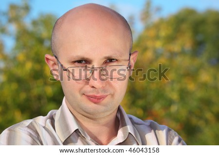 handsome man with glasses in fall park looking at camera - stock photo