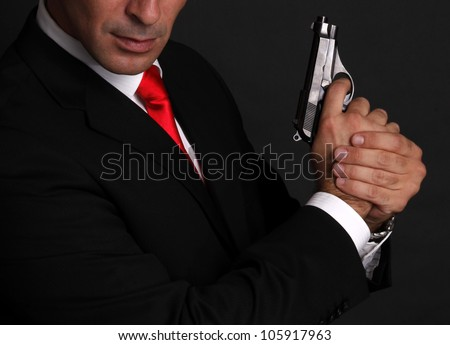 Handsome man with gun elegant spy - stock photo