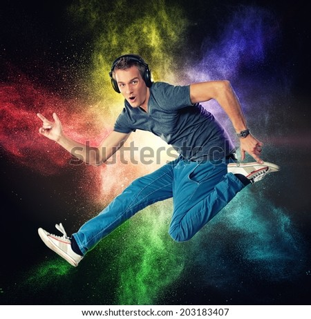 Handsome man with headphones jumping against colourful powder explosion  - stock photo