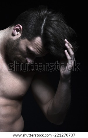 Handsome man with muscles with hand in his hair - stock photo