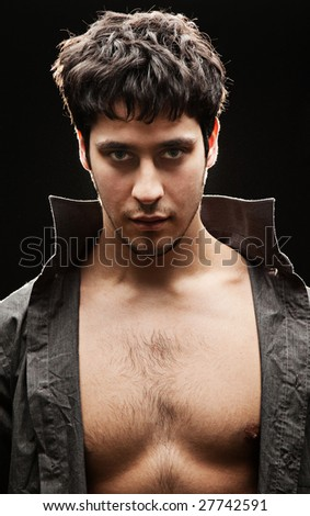 handsome man with naked breast against black background - stock photo