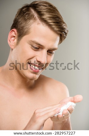 Handsome man with naked torso smiling and applies cream on his face. - stock photo