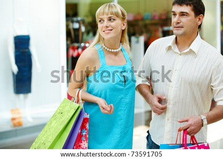 Handsome man with paperbags and his girlfriend in shopping mall - stock photo