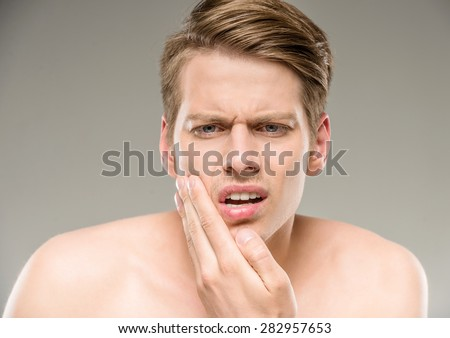 Handsome man with pure skin touching his face. - stock photo