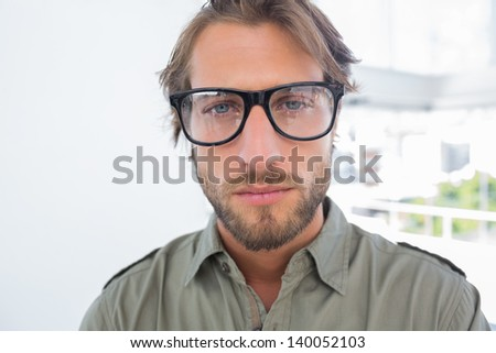 Handsome man with reading glasses looking at the camera - stock photo