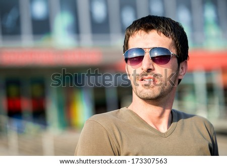 Handsome man with shades posing outdoor - stock photo