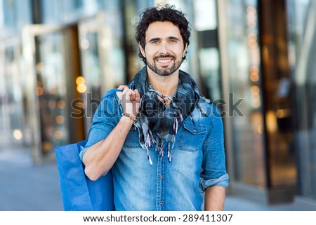 Handsome man with shopping bags walking outdoors - stock photo