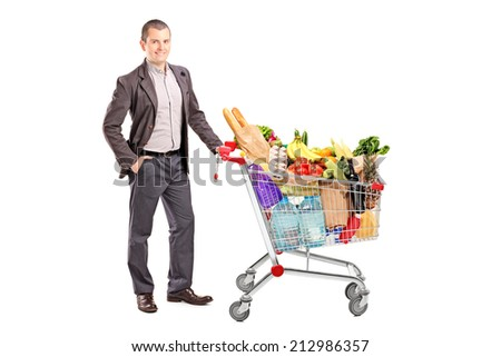Handsome man with shopping cart full of groceries isolated on white background - stock photo