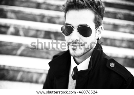 Handsome man with sunglasses staring at camera (piercing in lips and ear) - stock photo