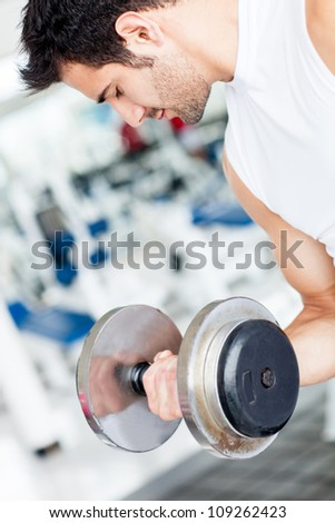 Handsome man working out at the gym lifting weights - stock photo