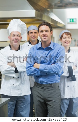 Handsome manager posing with some chefs in a kitchen - stock photo