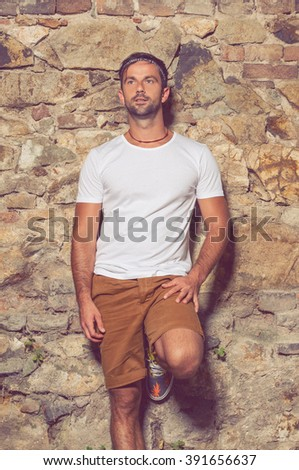 Handsome masculine man leaning against stone wall outdoors and looking away - stock photo