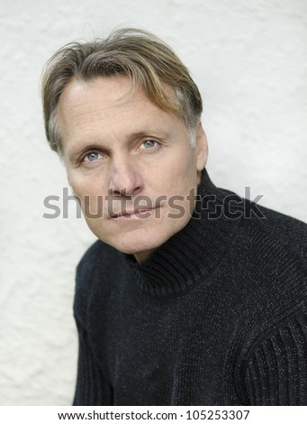 handsome mature blond man in his forties wearing a black sweater. - stock photo