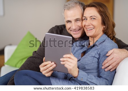 Handsome mature couple seated together on white couch in their living room with tablet smile at camera - stock photo