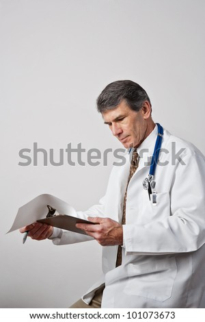 Handsome mature male doctor reviewing his notes with clipboard and pen. Plain gray background. - stock photo