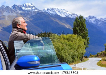 Handsome mature man standing on the road near opened door of his car during travel in New Zealand. - stock photo