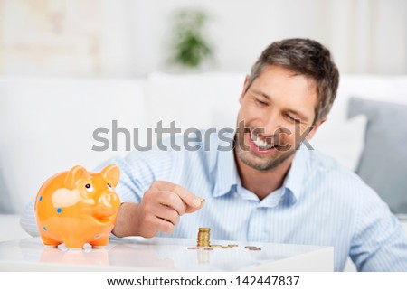 Handsome mature man with piggybank counting coins at table in house - stock photo