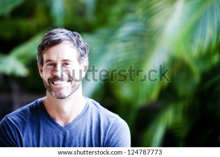 handsome maturing  man inviting smile - stock photo
