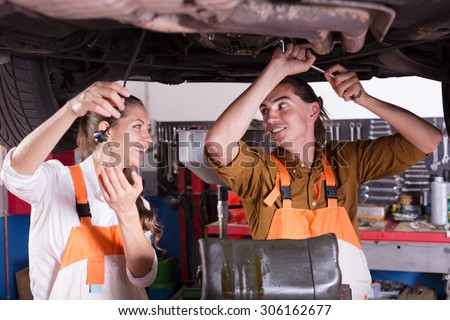 Handsome mechanic and beautiful female assistant working at auto repair shop  - stock photo