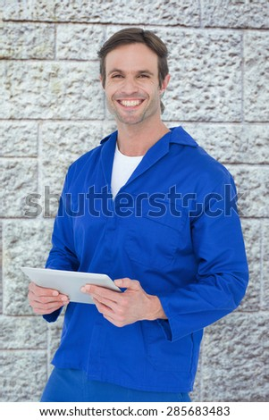 Handsome mechanic holding digital tablet against grey brick wall - stock photo