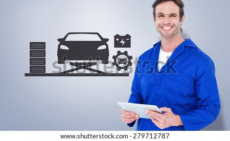 Handsome mechanic holding digital tablet against grey vignette - stock photo