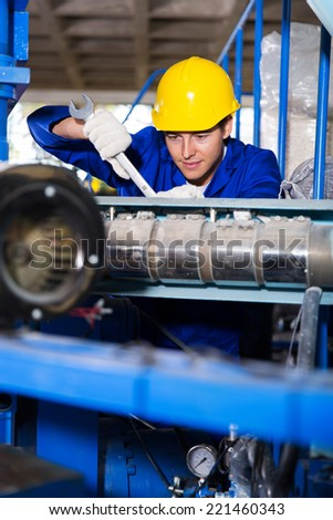 handsome mechanic repairing machine with spanner - stock photo