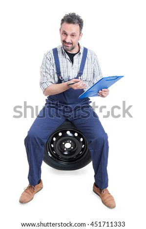 Handsome mechanic sitting on tire and holding clipboard as checking concept isolated on white - stock photo