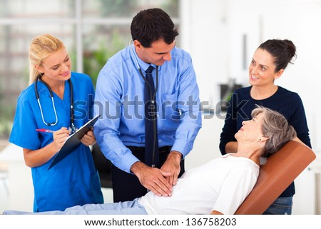 handsome medical doctor examining senior patient on examining bed - stock photo