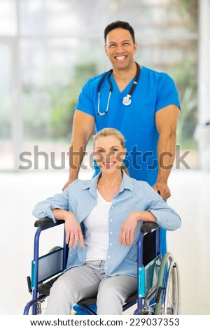 handsome medical male nurse taking care of senior patient in wheelchair - stock photo