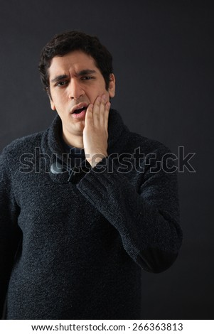 Handsome men doing different expressions in different sets of clothes: toothache - stock photo