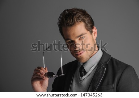 Handsome men. Portrait of handsome young men holding sunglasses while isolated on grey - stock photo