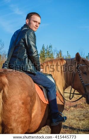 Handsome men riding a horse - stock photo