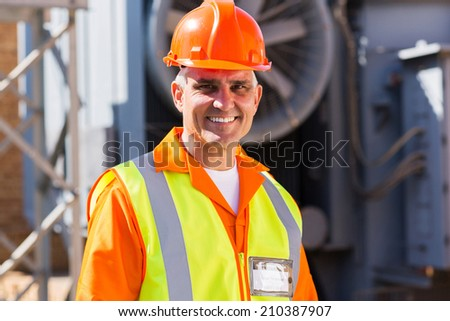 handsome mid age male electrician in electrical substation - stock photo
