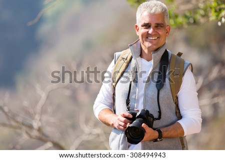 handsome mid age photographer standing in mountain valley - stock photo
