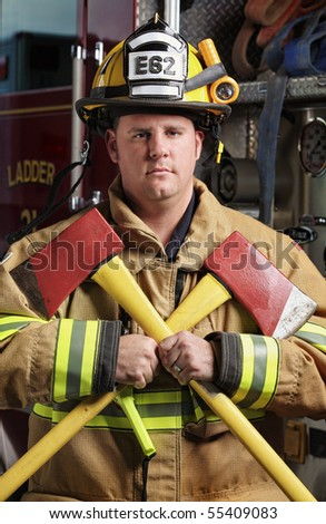 handsome middle age fireman wearing uniform and fire gear holding two axes standing in front of fire truck with serious face - stock photo