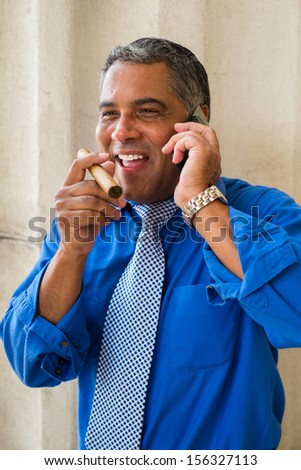 Handsome middle age Hispanic man smoking a cigar outdoors and speaking in a wireless phone in a urban setting. - stock photo