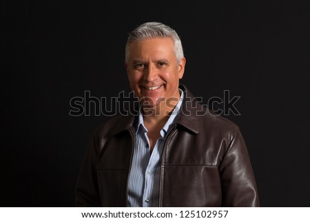 Handsome middle age man on a black background. - stock photo