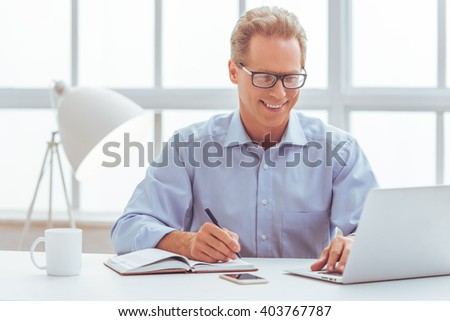 Handsome middle aged businessman in classic shirt and eyeglasses is using a laptop, taking notes and smiling while working in office - stock photo